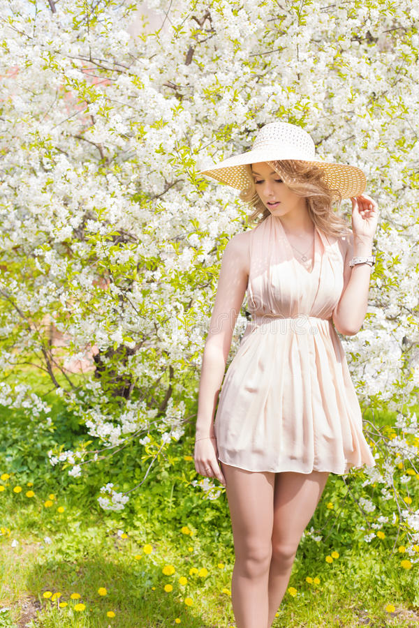 Härlig le söt flicka med långt blont lockigt hår som bär en hatt med stora fält i sommarrosa färgsundress royaltyfri fotografi