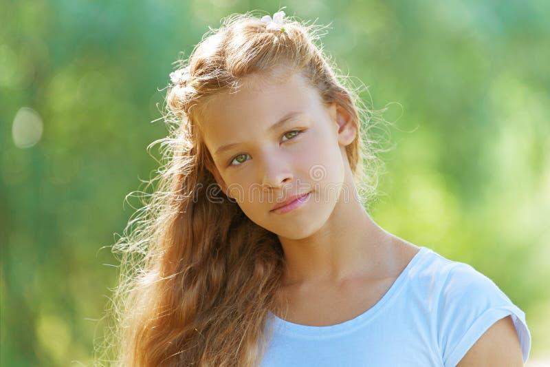Härlig le tonårs- flicka i den vita blusen royaltyfri fotografi