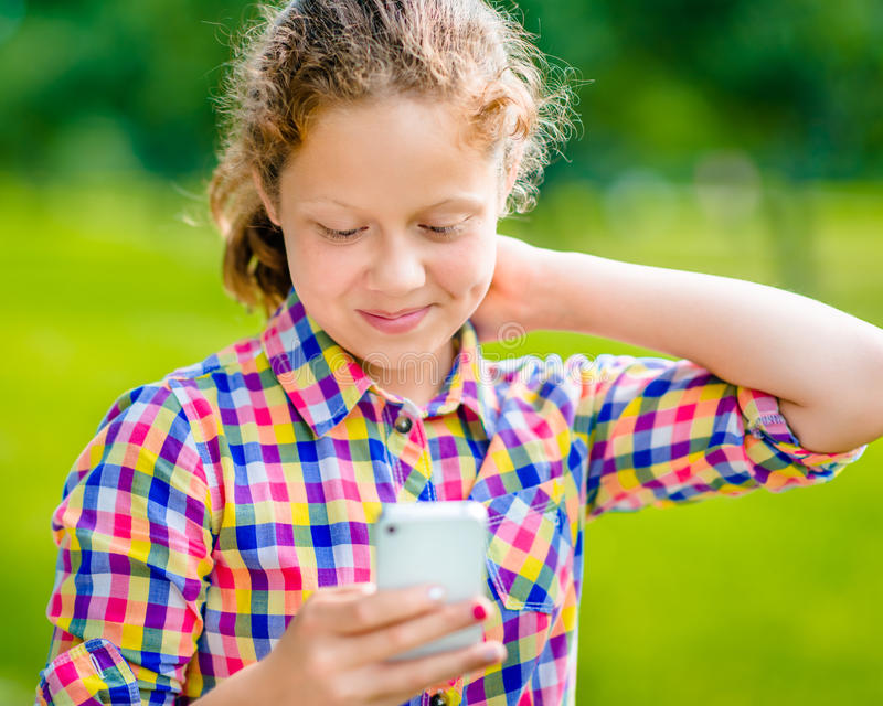 Härlig le tonårs- flicka i tillfällig kläder med smartphonen arkivbild