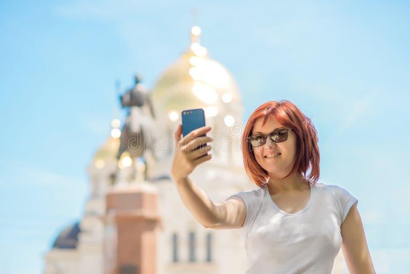 Härlig le turist- kvinnainnehavsmartphone och tafoto på stadsfyrkant eller gata i solig dag Semester och lopp arkivbild