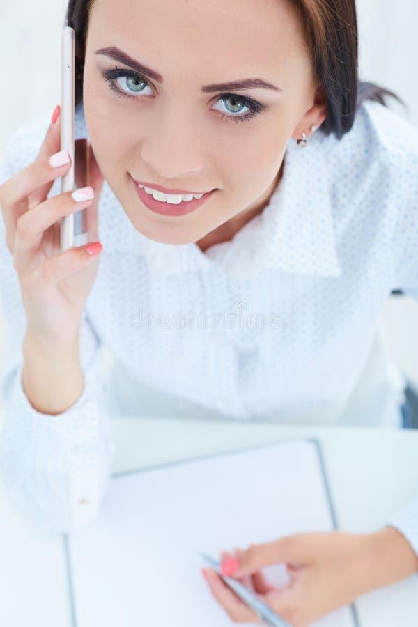 Härlig le ung flicka som talar på mobiltelefonen i kontoret arkivbild