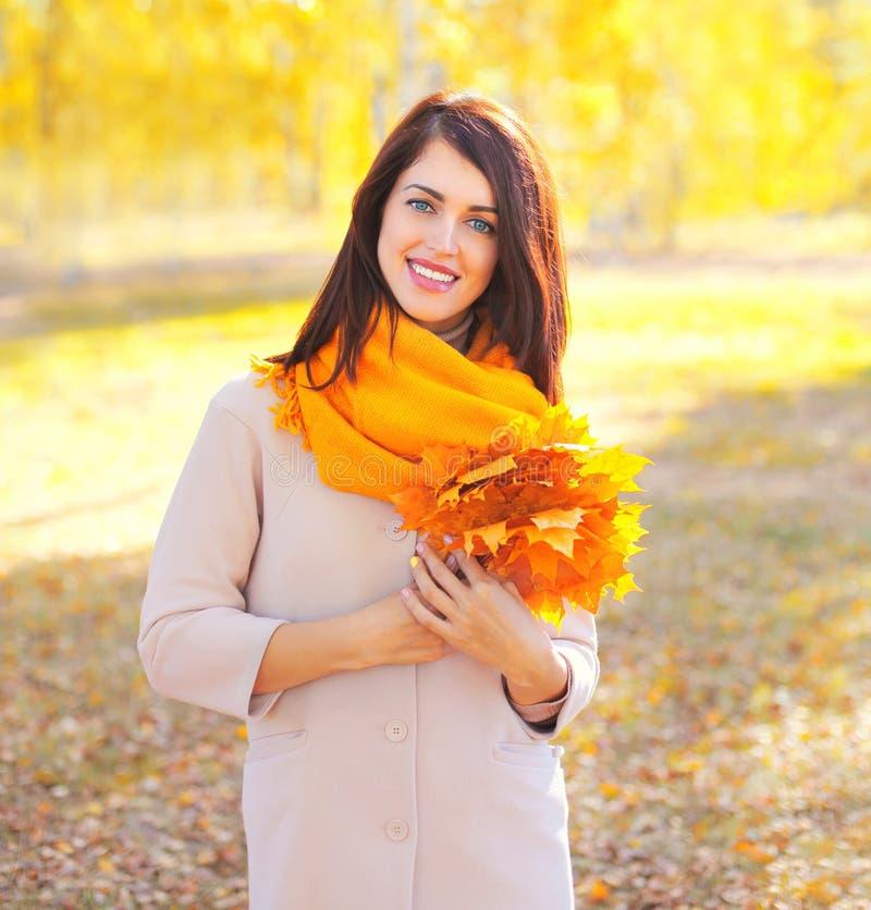 Härlig le ung kvinna för stående med gula lönnblad i solig höst arkivfoton