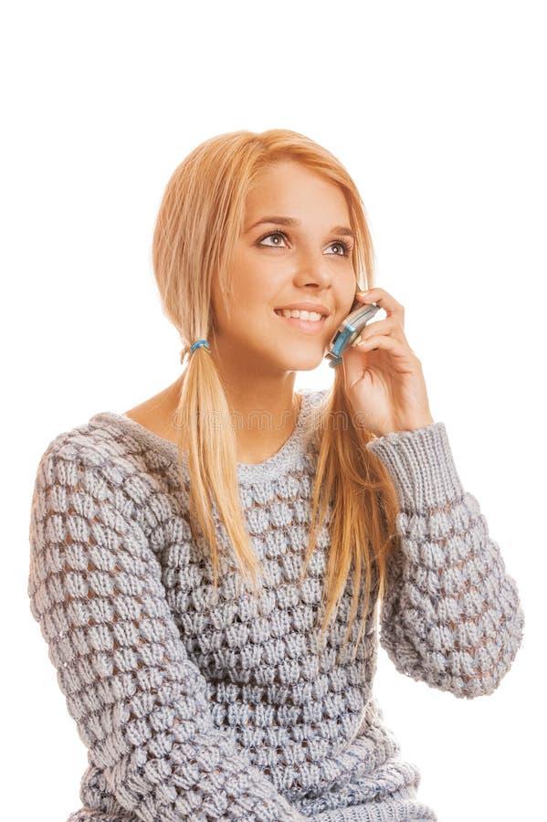 Härlig le ung kvinna i grå tröja som talar på en mobil arkivfoton