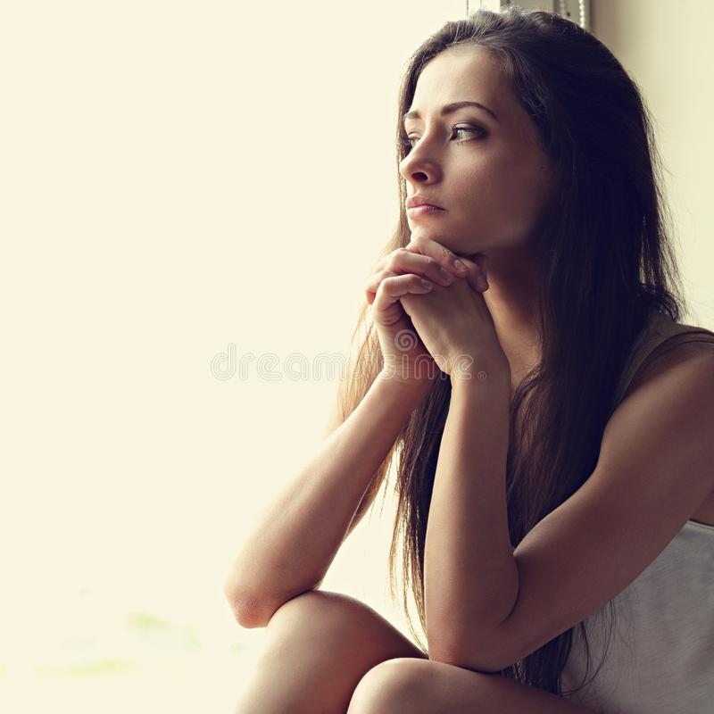Härlig ledsen ensam kvinna som omkring sitter och tänker, och lookin royaltyfria foton