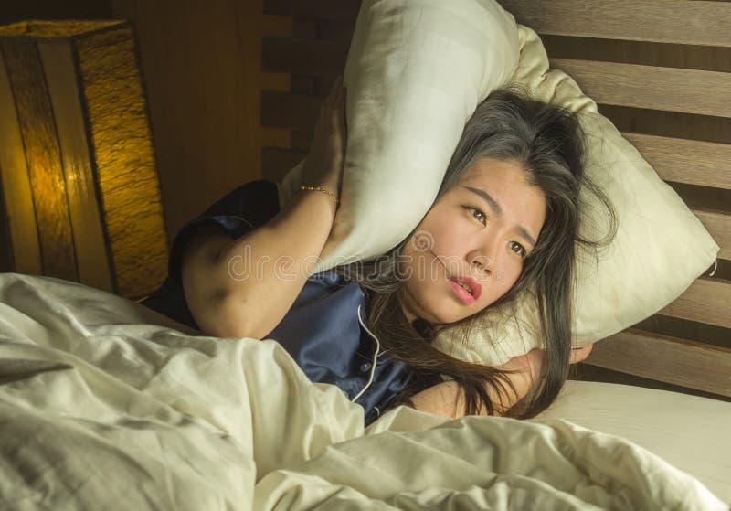 Härlig ledsen och deprimerad asiatisk kinesisk kvinna som är vaken i natten för säng som sent - lider ångestkris och fördjupnings royaltyfria foton