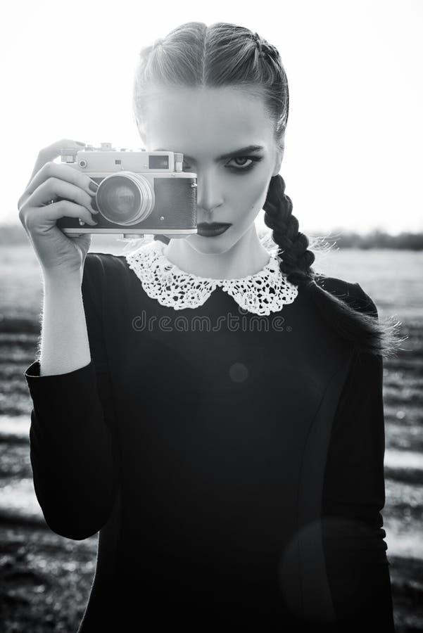 Härlig ledsen ung flicka som fotograferar på tappningfilmkamera svart white fotografering för bildbyråer
