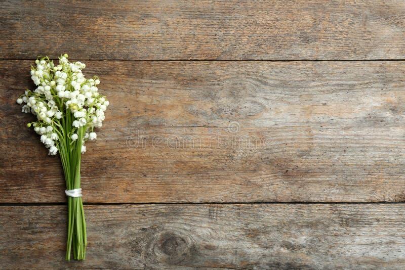 Härlig liljekonvaljbukett på träbakgrund, bästa sikt royaltyfri foto