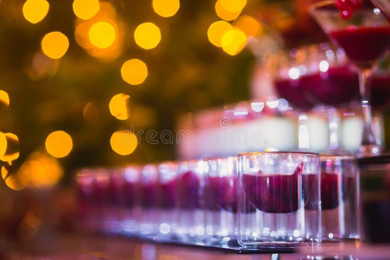 Härlig linje av olika kulöra alkoholcoctailar med rök på ett julparti, en tequila, en martini, en vodka och andra på delen arkivfoton