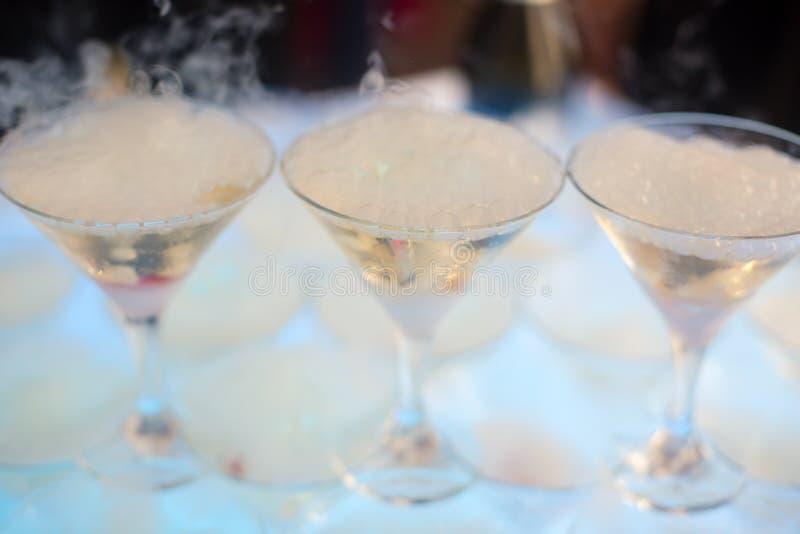 Härlig linje av olika kulöra alkoholcoctailar med rök på ett julparti, en tequila, en martini, en vodka och andra på delen royaltyfria foton