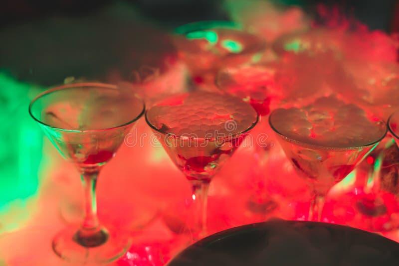 Härlig linje av olika kulöra alkoholcoctailar med rök på ett julparti, en tequila, en martini, en vodka och andra på delen arkivbilder