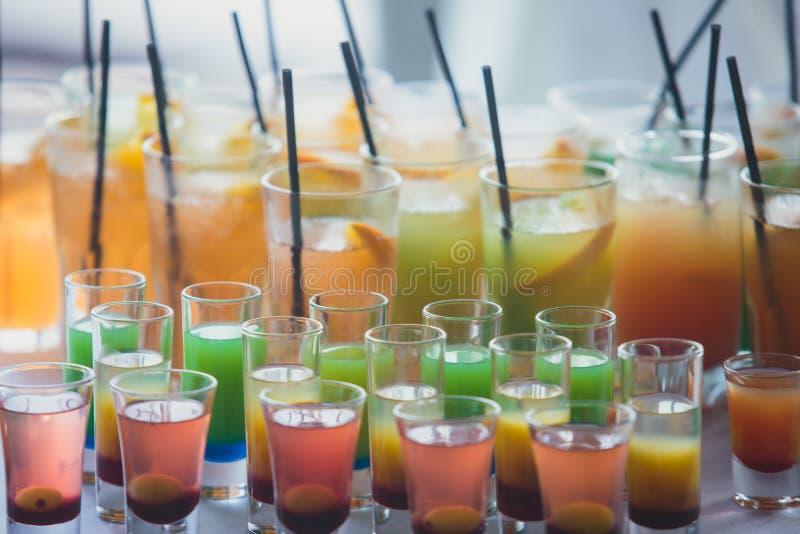 Härlig linje av olika kulöra alkoholcoctailar med rök på ett julparti, en tequila, en martini, en vodka och andra på delen arkivfoto