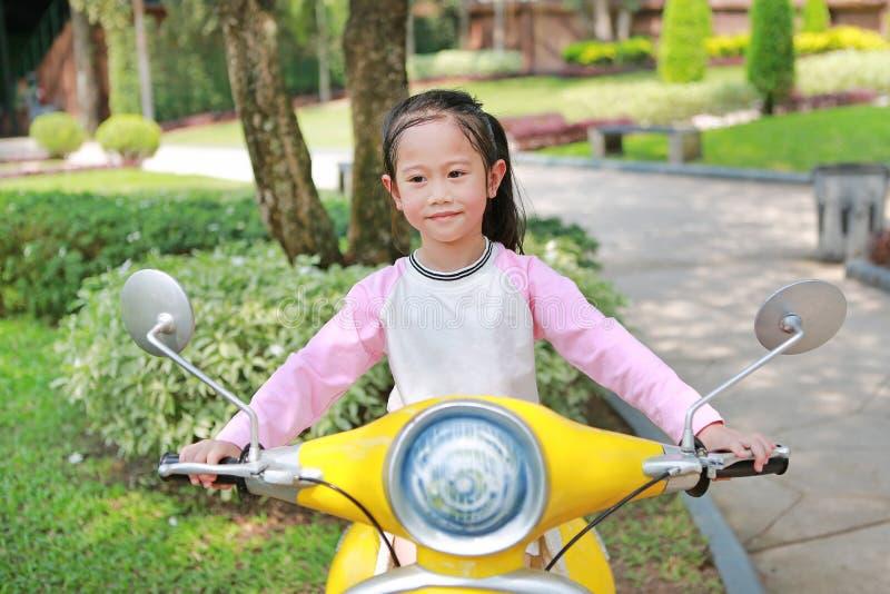 Härlig liten asiatisk barnflickaridning på garneringmotorcykeln i trädgården royaltyfri fotografi
