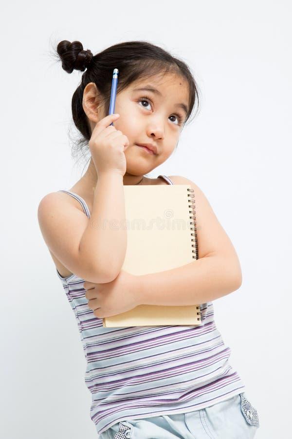 Härlig liten asiatisk flicka som tänker med blyertspennan och anteckningsboken arkivfoton