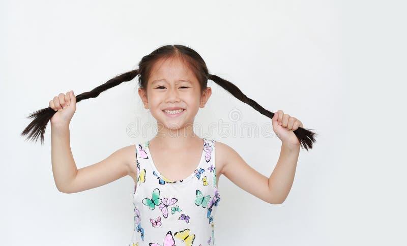 H?rlig liten asiatisk r?ttsvans f?r barnflickainnehav p? vit bakgrund St?ende som ler barn med tv? r?ttsvansar fotografering för bildbyråer