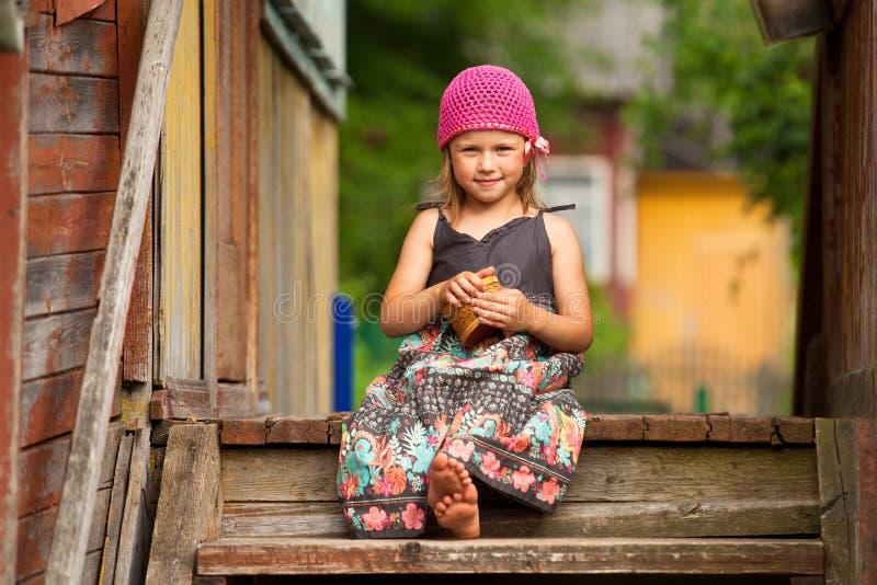 Härlig liten fem-år flicka på farstubron av en by fotografering för bildbyråer
