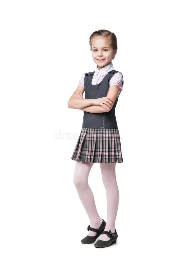 Härlig liten flicka i den isolerade skolalikformign royaltyfria bilder