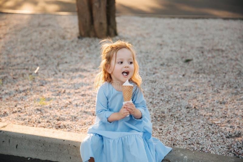 Härlig liten flicka i en blå klänning som äter en glass arkivfoto