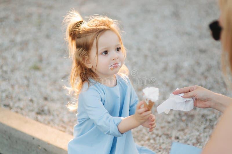Härlig liten flicka i en blå klänning som äter en glass royaltyfri bild