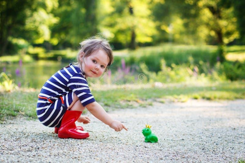 Härlig liten flicka i röda regnkängor som spelar med den rubber grodan royaltyfria foton