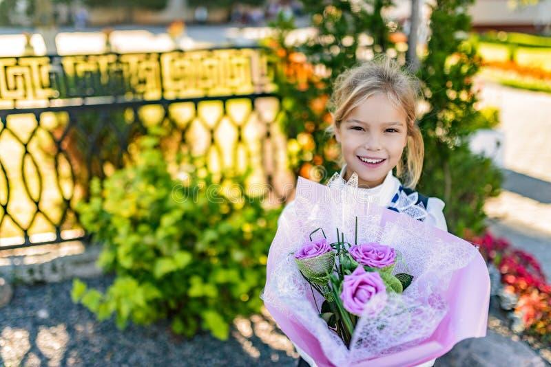 Härlig liten flicka med den stora buketten av blommor arkivbilder