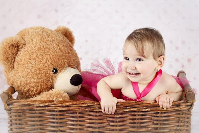 Härlig liten flicka med den stora nallebjörnen i den vide- korgen fotografering för bildbyråer