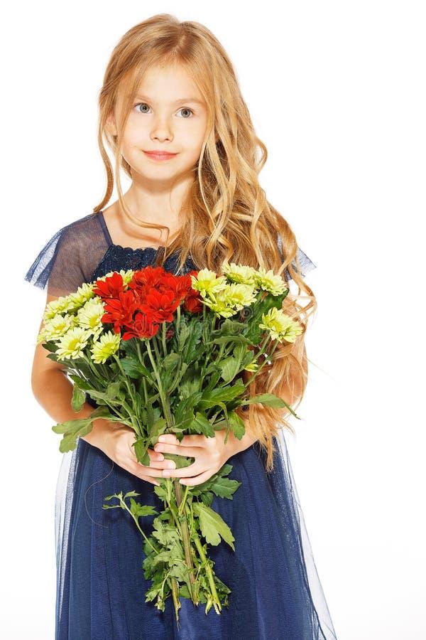 Härlig liten flicka med en bukett av blommor arkivfoto