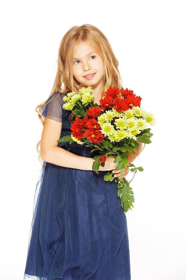 Härlig liten flicka med en bukett av blommor royaltyfri foto