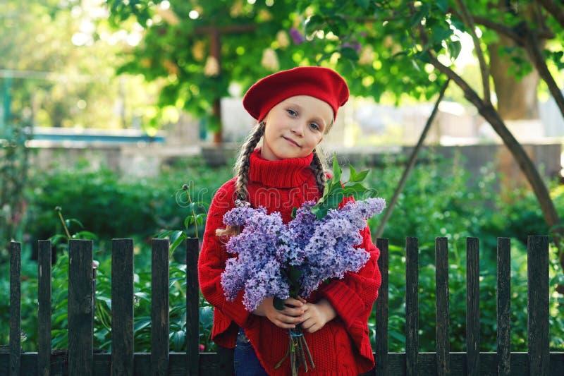 Härlig liten flicka med en bukett av lilor royaltyfria bilder