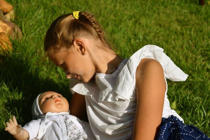 Härlig liten flicka med en docka i sommaren i en trädgård arkivfoto