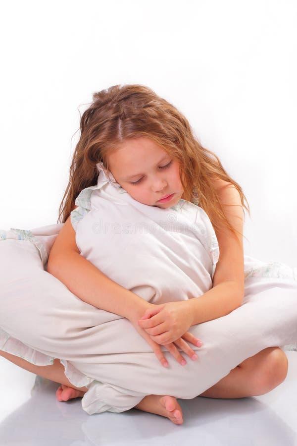 Härlig liten flicka med en kudde arkivfoto