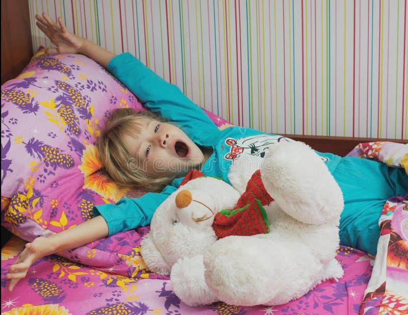 Härlig liten flicka med en leksakisbjörn royaltyfria foton