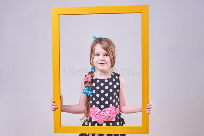 Härlig liten flicka, med ett roligt uttryck på hans framsida som rymmer en gul ram royaltyfria bilder