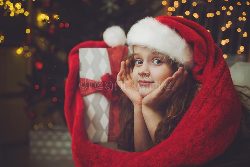Härlig liten flicka med gåvan och i jultomtenhatt arkivbilder