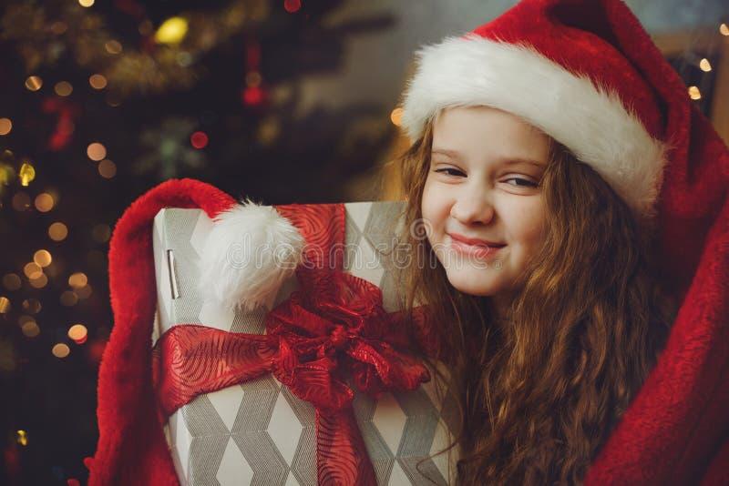 Härlig liten flicka med gåvan och i jultomtenhatt royaltyfri fotografi