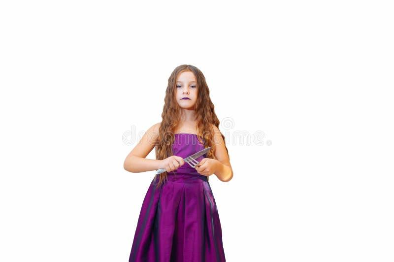Härlig liten flicka med långt hår i klänning, ståenden poserar med känslomässigt en kniv, och gaffeln för afton som isoleras arkivfoto