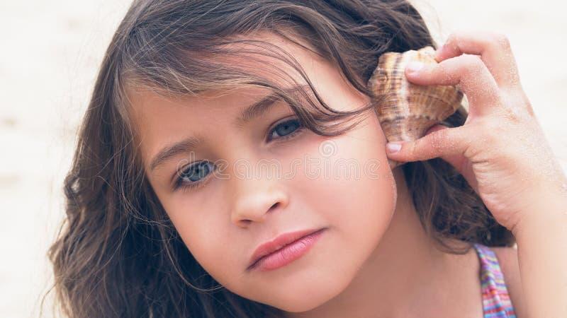 Härlig liten flicka med långt lockigt hår som lyssnar till havsmusik i cockleshell på stranden arkivbilder