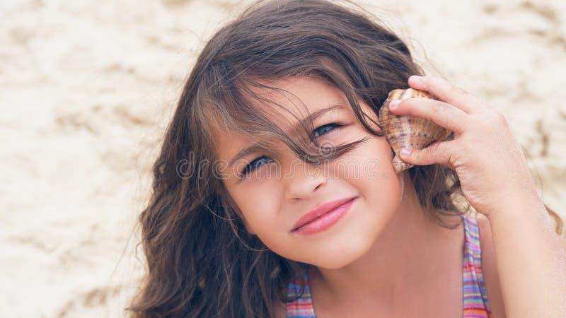 Härlig liten flicka med långt lockigt hår som lyssnar till havsmusik i cockleshell på stranden royaltyfria foton