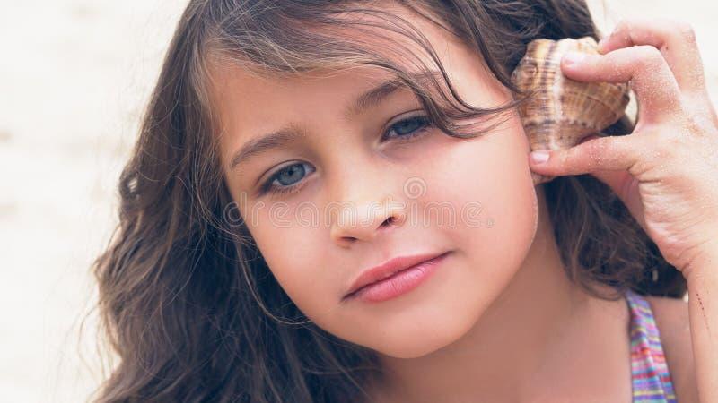 Härlig liten flicka med långt lockigt hår som lyssnar till havsmusik i cockleshell på stranden arkivfoto