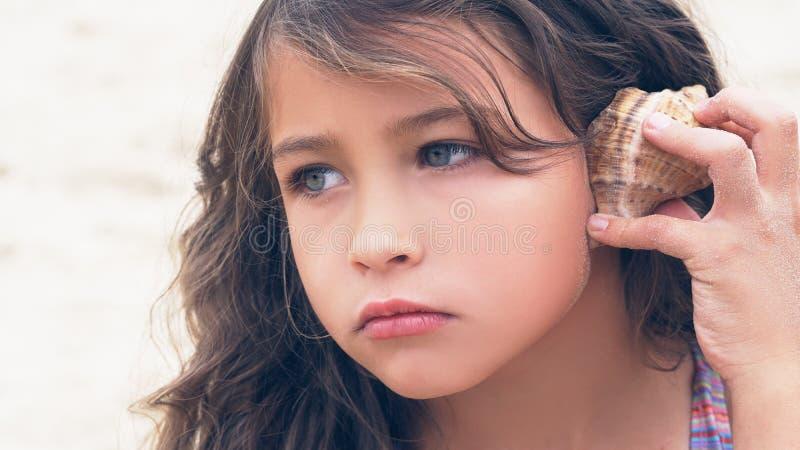 Härlig liten flicka med långt lockigt hår som lyssnar till havsmusik i cockleshell på stranden royaltyfri fotografi