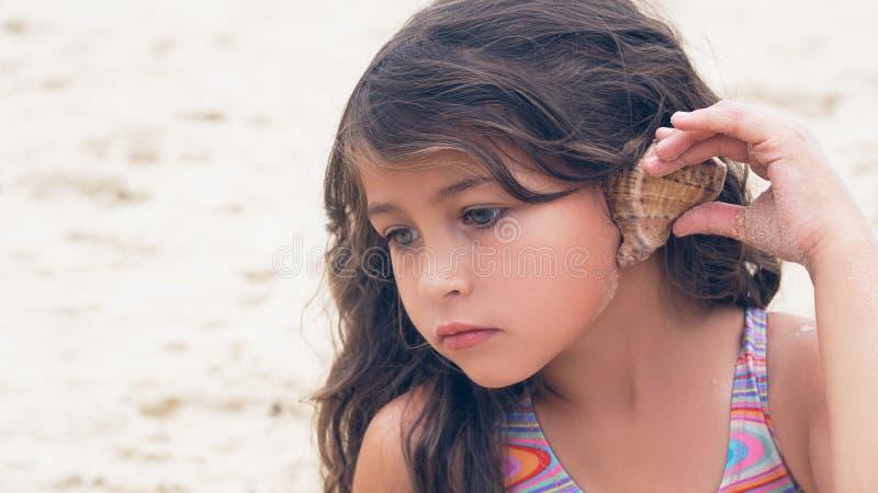 Härlig liten flicka med långt lockigt hår som lyssnar till havsmusik i cockleshell på stranden royaltyfri bild