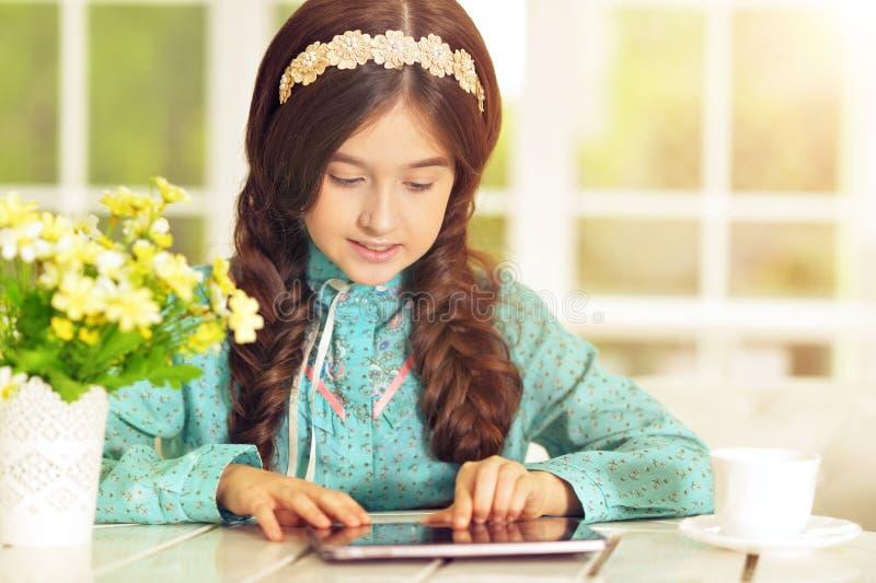 Härlig liten flicka med minnestavlaPC arkivbilder