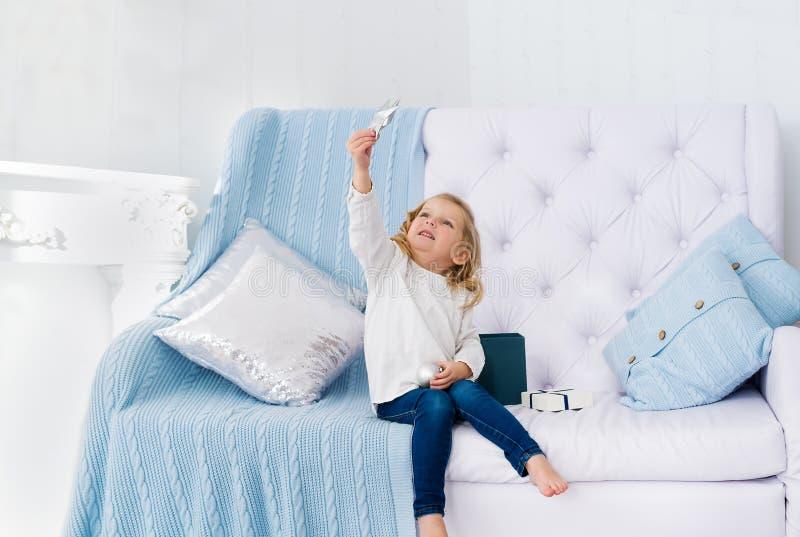Härlig liten flicka med stjärnan som sitter på soffan i vitt rum arkivbild