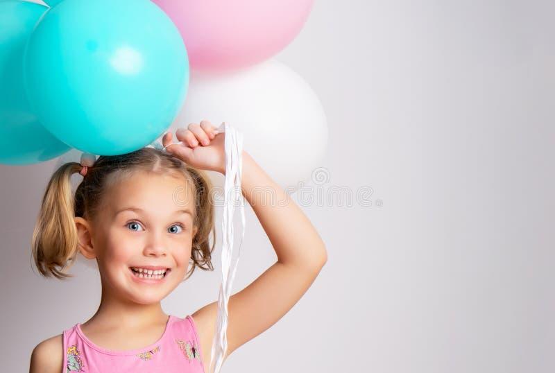 Härlig liten flicka och ljusa ballonger royaltyfri bild
