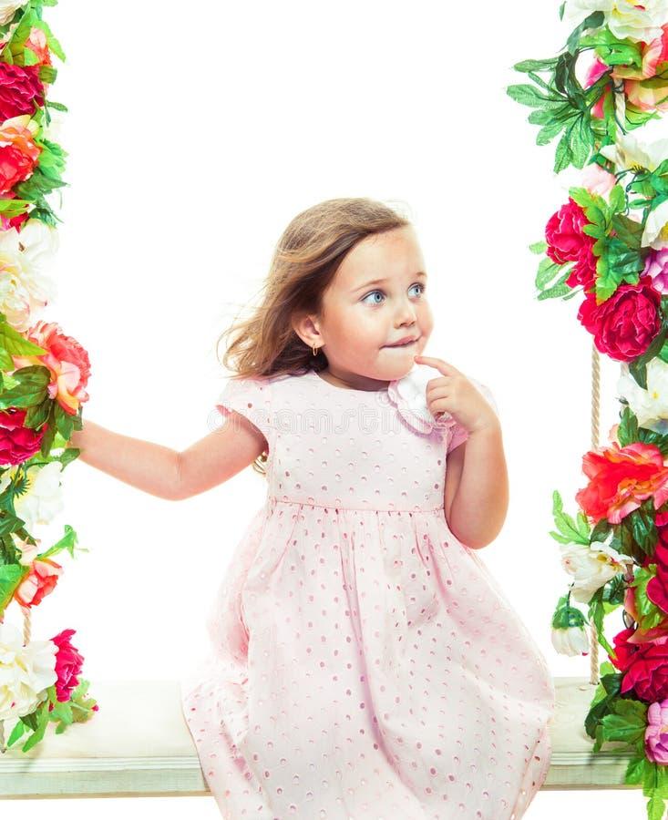 Härlig liten flicka på en gunga royaltyfri foto