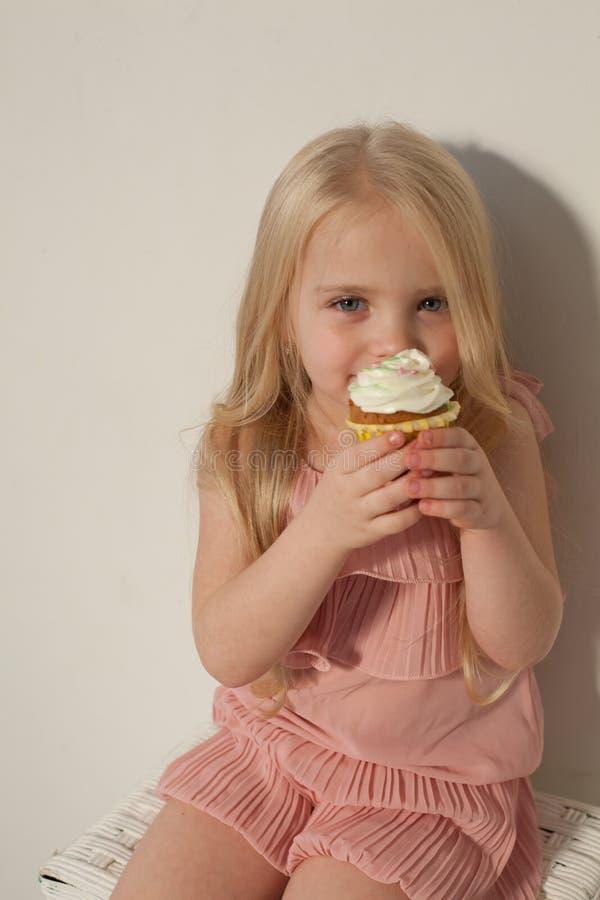 Härlig liten flicka som äter den söta godisklubbakakan arkivbild