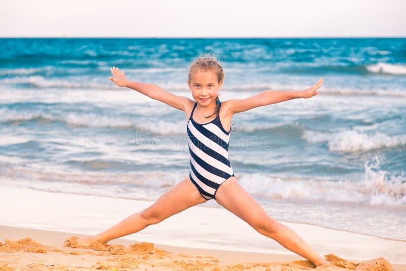 Härlig liten flicka som excercising på stranden royaltyfri bild
