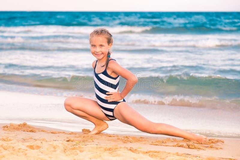 Härlig liten flicka som excercising på stranden arkivbilder