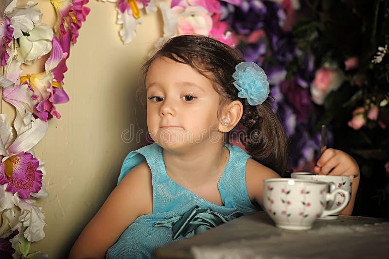 Härlig liten flicka som har en tebjudning arkivfoto