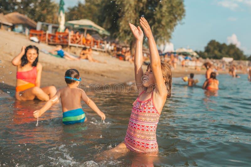 Härlig liten flicka som har gyckel i vatten fotografering för bildbyråer