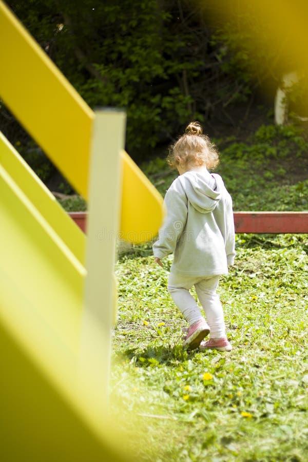 Härlig liten flicka som kör runt om lekplatsen från hennes moder arkivfoto